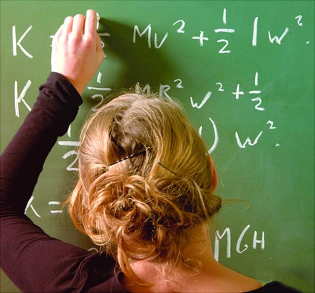 Mädchen an der Tafel schreibt eine mathematische Fomel