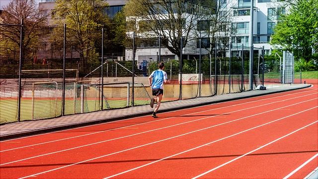 Ein junger Mann läuft auf einer roten Tartanbahn