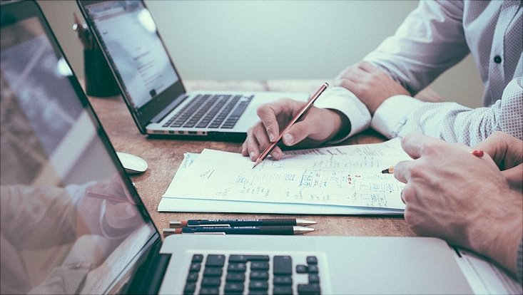 Zwei Männer schreiben auf einem Blatt Papier. An der Seite steht jeweils ein Laptop.