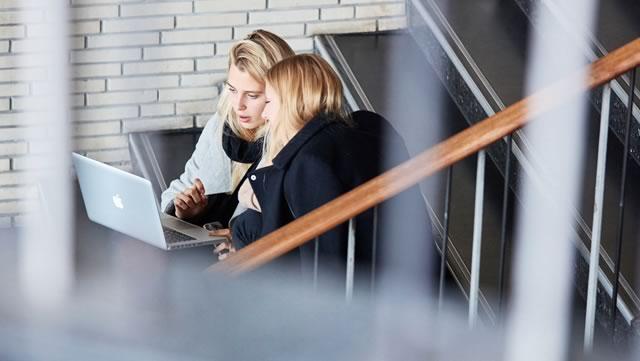 Personen unterhalten sich und schauen gemeinsam auf ein Notebook.