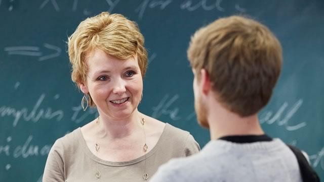 Zwei Personen in einem Dialog miteinander vor einer Tafel.