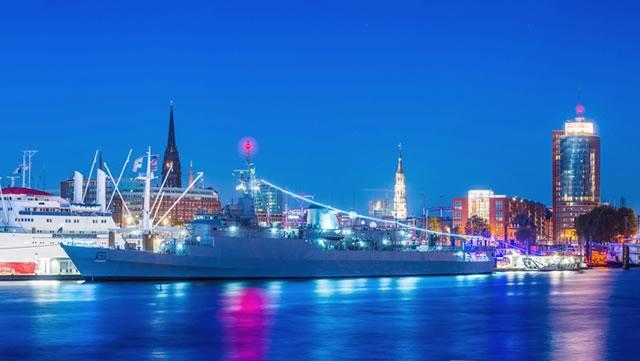 Hamburger Hafen in der Dämmerung. Man sieht Schiffe, die Elbphillarmonie und einige weitere Gebäude der Hafen-City.