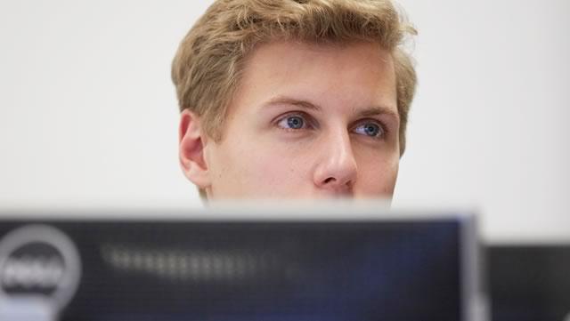 Eine Person sitzt vor einem Computer und schaut in eine bestimmte Richtung.