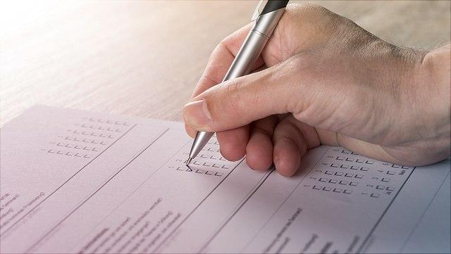 Hand mit Stift füllt einen Fragebogen aus
