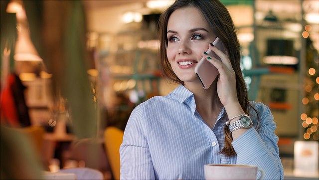 Frau telefoniert mit Handy, vor ihr steht eine Tasse Kaffee
