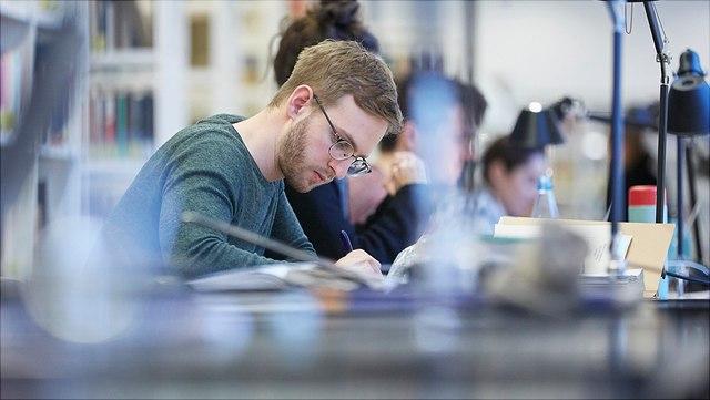 Mann mit Brille sitzt in einer Bibliothek und schreibt konzentriert, Seitenansicht
