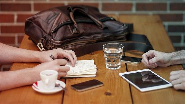 Tisch mit Tasche, Kaffeetasse und Wasserglas, man sieht die Hände von zwei Personen auf dem Tisch liegen