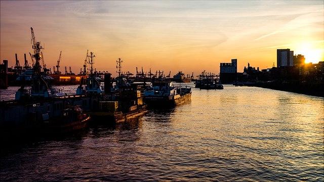 Hafen im Sonnenuntergang, mit vielen Schiffen und Gebäuden.