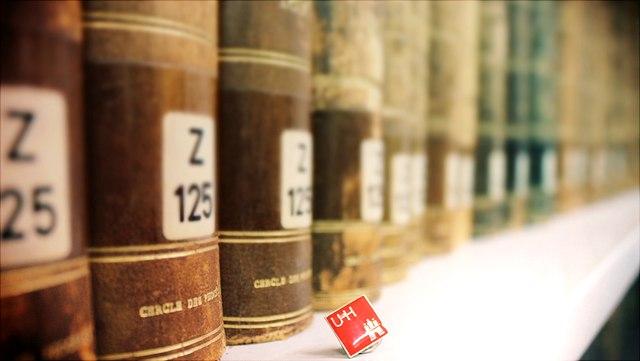 Bücherregal mit verschiedenen Büchern und einem Universität Hamburg Stecker vor einem der Bücher, im Bücherregal.