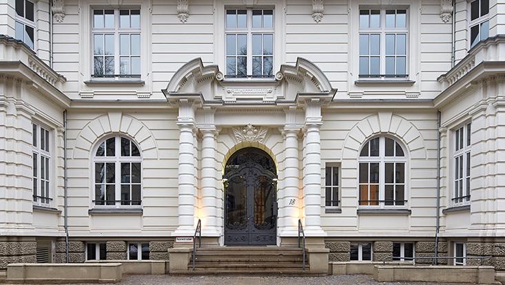 """Hauseingang mit der Hausnummer 18 und zwei weißen Säulen. Rechts neben der großen Tür in anthrazit ist ein großes Fenster. Vor der Tür sind für die paar Treppnstufen zwei grauen Geländer angebaut. Links unten ist ein """"Feuerwehrzufahrt""""-Schild."""