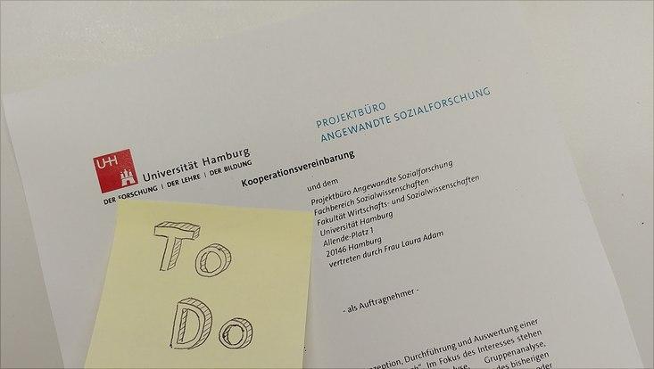 """Kooperationsvereinbarung mit einem gelben Klebezettel, auf dem """"To Do"""" steht"""