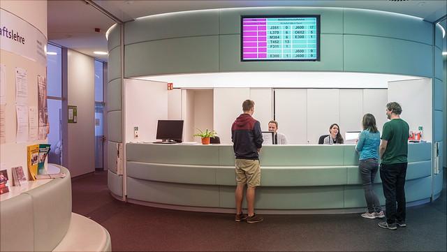 Am Tresen des Studienbüros der Betriebswirtschaftslehre stehen drei Personen. Über dem Tresen ist ein Monitor mit Aufruf- und Raumnummern befestigt.