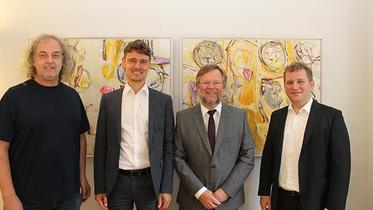 Die dekanatsmitglieder stehen nebeneinander von einer Wand mit zwei Bildern der Künstlerin Elke Wree. Von links nach rechts sind zu sehen Prodekan Prof. Stefan Voß, Dekan Prof. Schreyögg, Studiendekan Prof. Grotherr und Forschungsdekan Prof. Voigt.