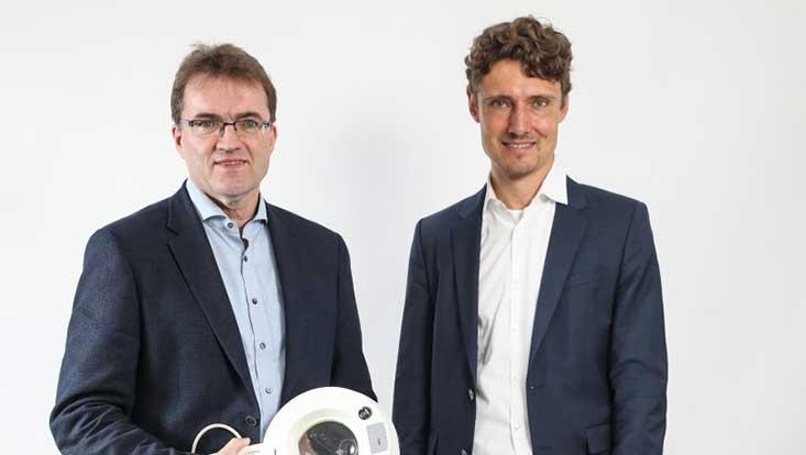 Prof. Dr. Matthias Augustin steht links neben Prof. Dr. Jonas Schreyögg vor hellem Hintergrund. Beide sind bis zur Hüfte abgebildet.