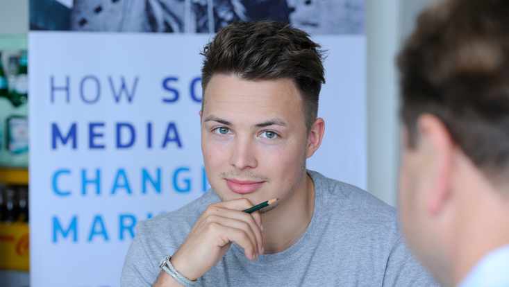 "Portrait eines Studenten, im Hintergrund Schriftzug ""How Social Media is changing Marketing"""