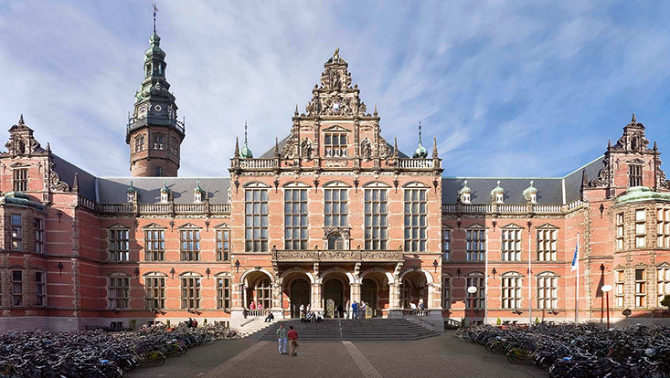 Frontansicht des Hauptgebäudes der Universität Groningen. Imposanter Rotklinkerbau. Auf dem Kopfsteinpflaster-Platz davor stehen unzählige Fahrräder.