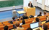 Hörsaal mit Lehrendem am Pult und Studierenden im Publikum