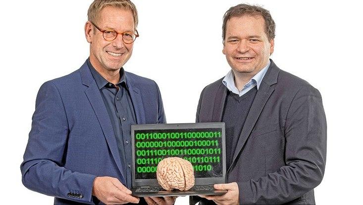 Prof. Dr. Christian Gerloff (links) und Prof. Dr. Martin Spindler halten einen Laptop, auf dessen Tastatur das Modell eines Gehirns tront. Auf dem Bildschirm ist eine Folge von grünen Nullen uns Einsen zu sehen.