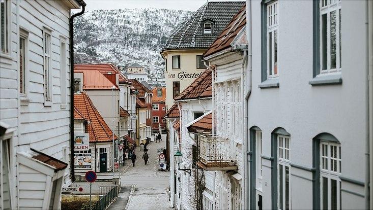 Eine ruhige Straße, in der ein paar Menschen spazieren gehen, im Hintergrund sieht man Schneebedeckte Berge mit Bäumen