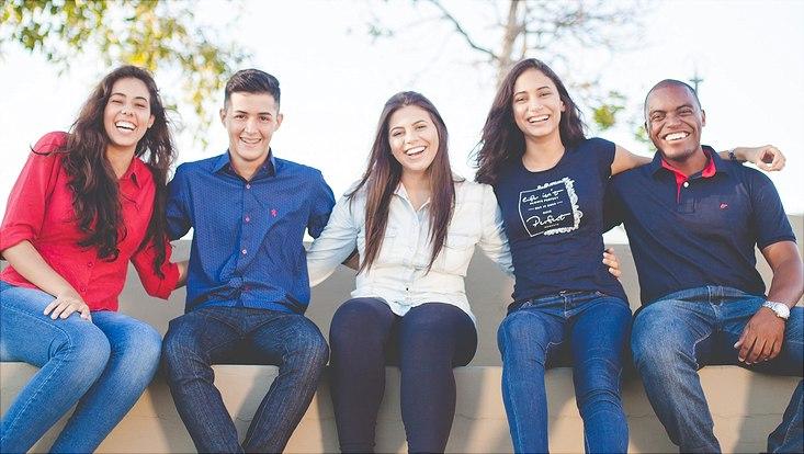 Fünf junge Erwachsene verschiedenen Geschlechts und Herkünfte sitzen nebeneinander, halten sich umarmt und lachen in die Kamera