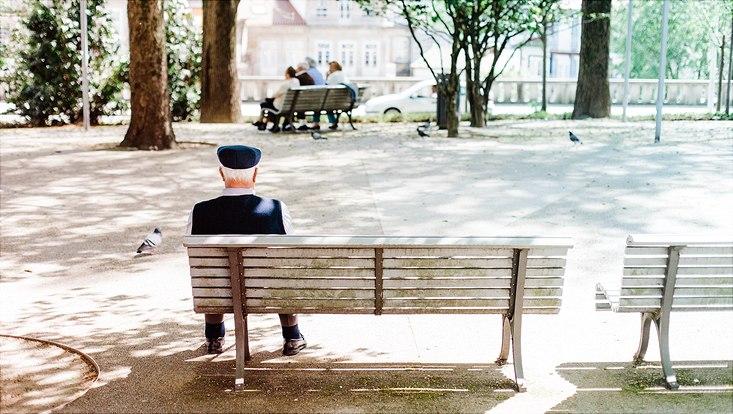 Alter Mensch sitzt einsam auf einer Bank im Park