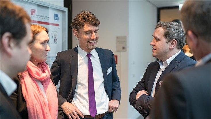 Dieses Bild zeigt eine Gruppe in der sich Prof. Dr. Jonas Schreyögg mit Dr. Gottfried Ludewig unterhält.
