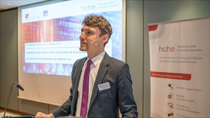 Dieses Bild zeigt Prof. Dr. Jonas Schreyögg am Podium, er hält einen Vortrag.