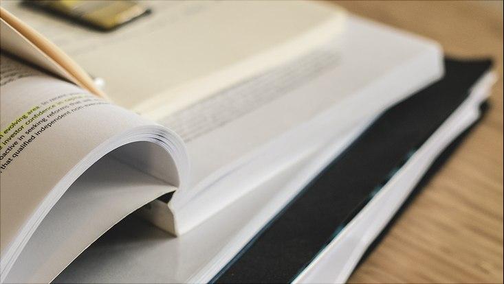 Gestapelte Bücher und Hefter, oberstes liegt geöffnet mit markierter Schrift auf