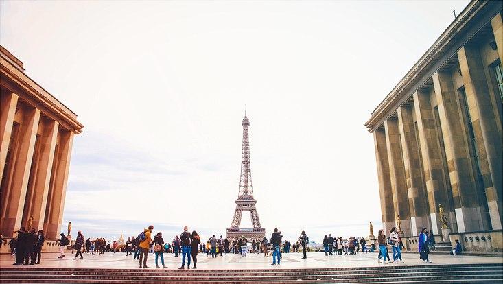 Menschen stehen auf einem großen Platz und schauen zum Eifelturm, der zentral im Hintergrund steht.