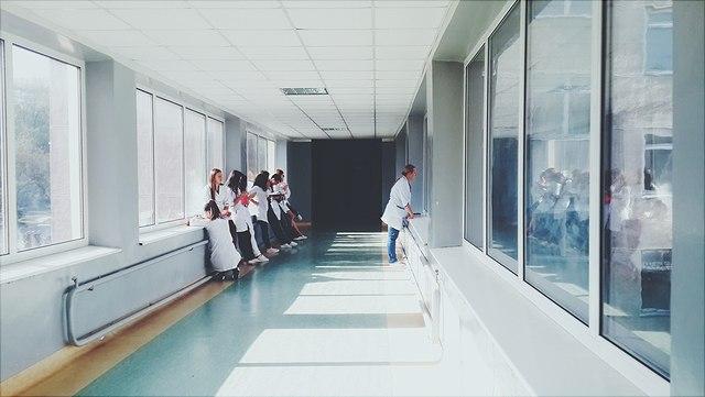 Auf diesem Bild ist ein Korridor zu sehen, an dessen Seiten sich jeweils mehrere Ärzte an die Wände anlehnen