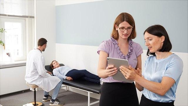 Auf diesem Bild besprechen sich zwei Personen am rechten Bildrand, während links im Hintergrund eine Person im Kittel mit einer Frau, die auf einer Liege liegt, redet.