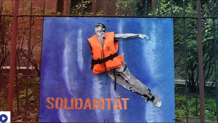 Installation mit Graffiti an einem Zaun zum Thema Solidarität