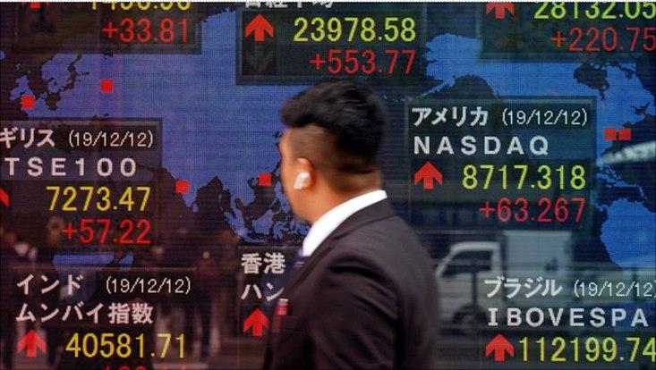 Banker in Tokio vor Wand mit Aktienkursen