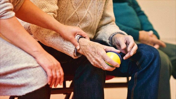 Junge Person unterstützt ältere Person und hält sie am Arm