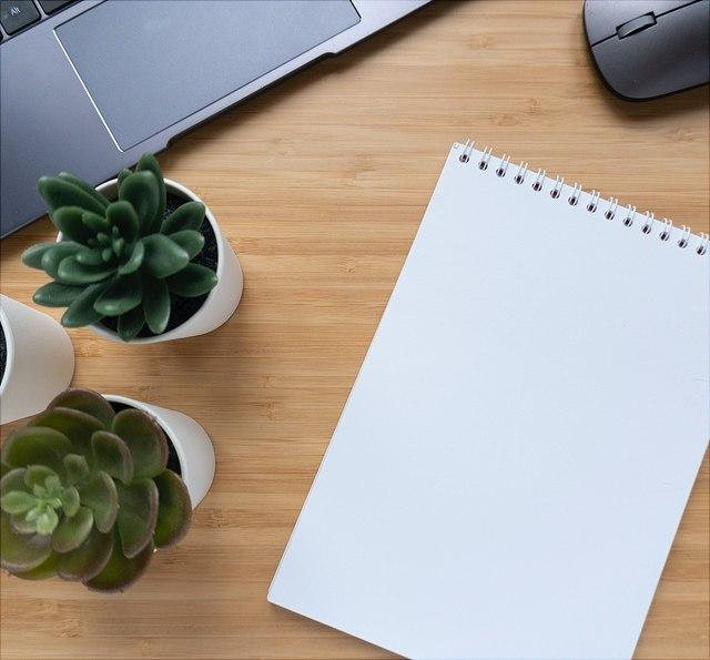 Schreibtisch mit Notizblock, PC und Pflanzen