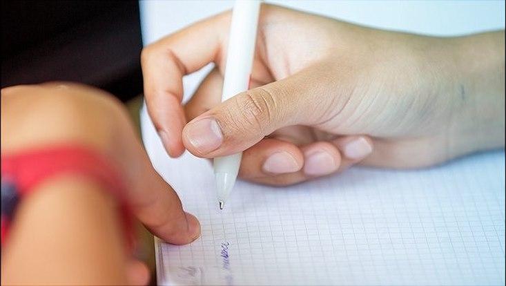 Rechte Hand mit weißem Kugelschreiber schreibt auf weißem karriertem Block