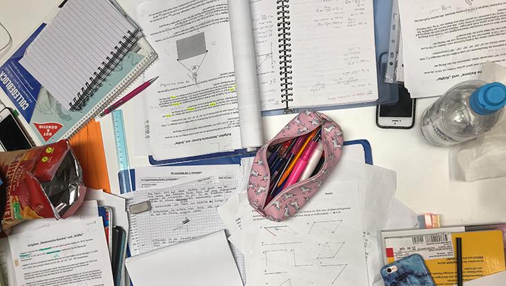 Schreibtisch mit vielen Unterlagen, Handy und Schreibutensilien