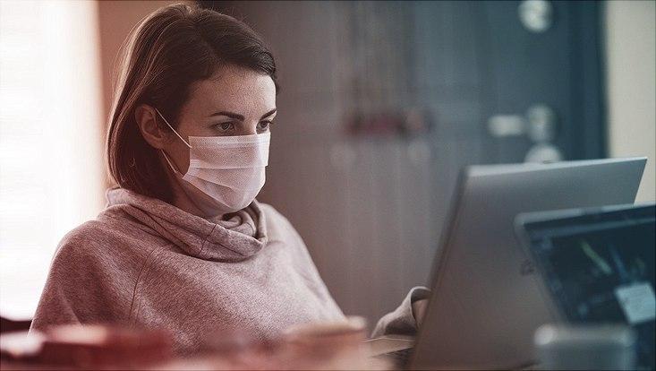 Am Computer mit Maske