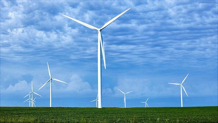 Wind turbines on green field in front of blue sky