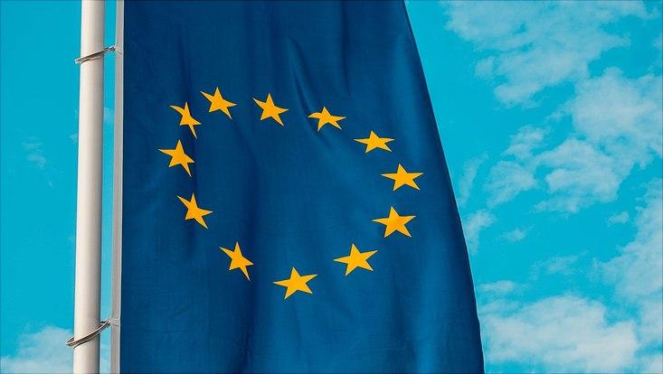 Wehende Europa-Flagge mit blauem, leicht bewölktem Himmel im Hintergrund