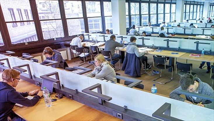 Studierende lernen an Schreibtischen im Lesesaal