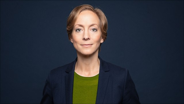 Female with short hair, green shirt and dark blue blazer (Prof. Schröder)
