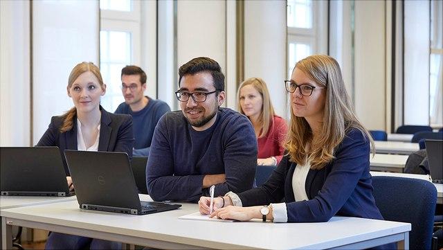 Hier sind fünf Menschen abgebildet, die zusammen in einem Seminarraum sitzen und in die Kamera lächeln.