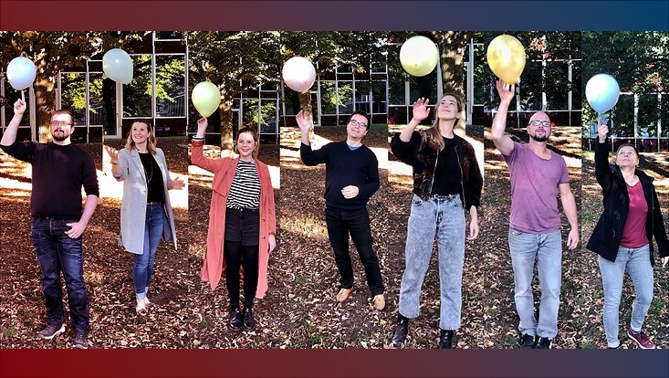 Mitarbeitende im Projektbüro mit Luftballons