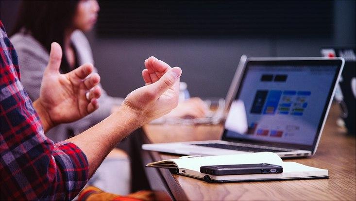 Schreibtisch mit Laptop und Notizblock, Hände von männlicher Person zu sehen