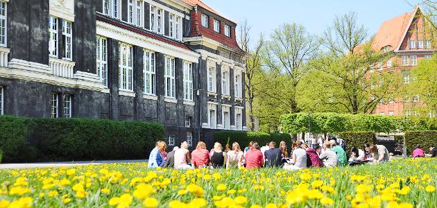 Studierende auf Wiese vor der Uni