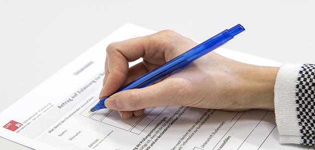 Eine Hand (mit Stift) füllt ein Formular aus