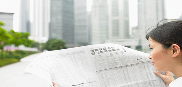 Frau liest eine chinesische Zeitung, im Hintergrund eine Skyline zu erkennen