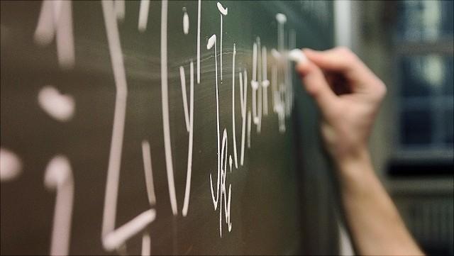 Detail einer Hand, die mit Kreide eine mathematische Formel an eine Tafel schreibt