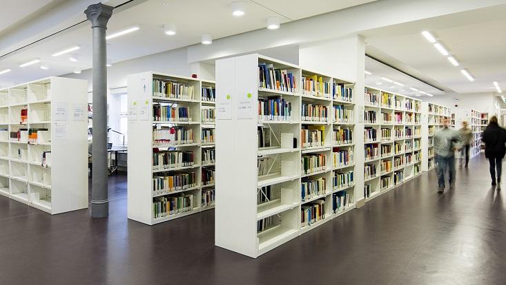 Regale mit Büchern, vorbeigehende Menschen/Shelves with books, people walking/